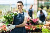 Propietario de vivero mujer feliz con maceta de flores en invernadero — Foto de Stock