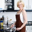 Stock Photo: Happy woman cooking in kitchen