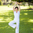 Beautiful middle aged woman doing yoga outdoors — Stock Photo #14902555