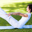 Middle aged woman doing yoga pose outdoors — Stock Photo #14902635