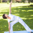 Healthy middle aged woman stretching outdoors — Stock Photo #14902643