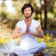 Stock Photo: Middle aged woman doing meditation by the pond