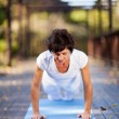 Mature woman doing push ups outdoors — Stockfoto