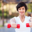 Happy middle aged woman exercise with dumbbells outdoors — Stock Photo #14903111