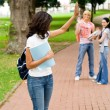 Female college student waving good bye to friends — Stockfoto