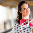 Young woman carrying shopping bags in mall — Stock Photo