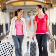 Two young women walking with shopping bags — Stockfoto