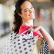 Happy young woman carrying shopping bags in mall — Stockfoto