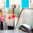 Two happy young women in shopping mall — Stock Photo