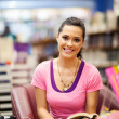 young woman reading a book in bookstore — Stock Photo #14904077