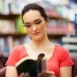Young woman reading a book in library — Stock Photo