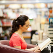 Young woman reading a book in bookstore — Stock Photo