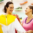 Two young women shopping for sportswear in mall — Stock Photo #14904219