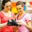 Royalty-Free Stock Photo: Shop assistant helping customer choosing sports shoes