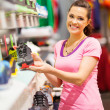 Royalty-Free Stock Photo: Happy young woman choosing sports shoes to buy in store