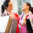 Happy friends shopping in mall — Stock Photo