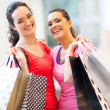 Happy girls with shopping bags in mall — Stock Photo