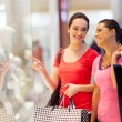 Happy young women window shopping in mall — Stock Photo
