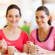 Two women friends having drinks in cafe - Stock Photo