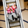 Happy shopping women on escalator with shopping bags — Stock Photo #14904517