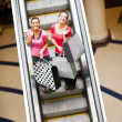 Happy shopping women on escalator with shopping bags — Stock Photo