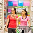 Two young women walking in supermarket with trolley - 图库照片