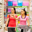 Stock Photo: Two young women walking in supermarket with trolley