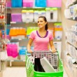 Young woman walking in supermarket aisle with trolley - 图库照片