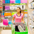 Young woman walking in supermarket aisle with trolley — Stock Photo
