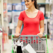 Happy young woman pushing a trolley in supermarket - Stockfoto