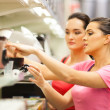 Young women shopping for appliance in supermarket — Stock Photo