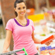 Happy young woman shopping for frozen food in supermarket - Stok fotoğraf