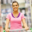 Happy young woman pushing a trolley in supermarket - Stok fotoğraf