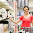 Stock Photo: Young womshopping for appliance in supermarket
