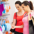 Stock Photo: Young woman shopping for lingerie in clothing store