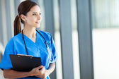 Beautiful young female medical intern looking outside window — Stock Photo