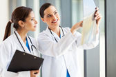 Two female medical doctors looking at patients x-ray — Stock Photo