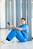 медицинский работник, сидя на полу больницы и с помощью планшетного компьютера — Стоковое фото