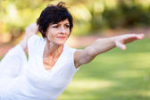 Healthy middle aged woman stretching outdoors — Stok fotoğraf