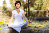 Middle aged woman doing yoga meditation outdoors — Stock Photo