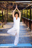 Beautiful mature woman yoga pose in garden — Stok fotoğraf