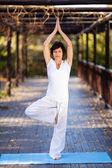 Schöne reife frau yoga-pose im garten — Stockfoto