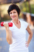 Happy middle aged woman exercise with dumbbells — Stock Photo
