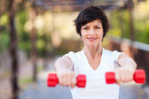 Happy middle aged woman exercise with dumbbells outdoors — Stock Photo