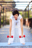 Happy middle aged woman working out with dumbbells — Stock Photo