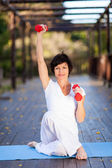 Beautiful middle aged woman exercise with dumbbells — Stock Photo