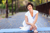 Fit middle aged woman relaxing after workout — Stock Photo