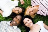 группа молодых разнообразия, лежа на траве — Стоковое фото