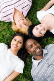 Group of young lying on grass — Stock Photo