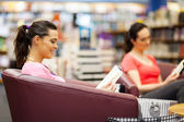 Joven leyendo un libro en librería — Foto de Stock